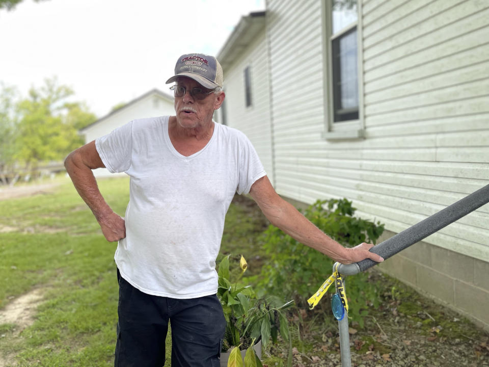 Jim Traylor stands outside his home, where he grew up and still lives, in Waverly, Tenn., Sept. 16, 2021. When record-setting downpours on Aug. 21 transformed a normally shallow stream into a raging wall of water, it gushed into his house and washed over the entire town, killing 20 people before it receded. Traylor's family got out safe, dogs and all, but the home his grandfather bought in 1921 may have seen its last days, barring help from the Federal Emergency Management Agency. He doesn't have the money to repair it and doesn't want a loan. (AP Photo/Jonathan Mattise)