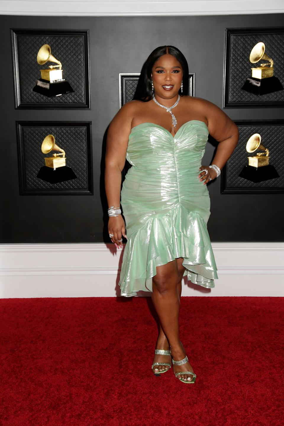 """The """"Truth Hurts'' singer rocked the Grammy red carpet wearing a seafoam green, '80s-inspired strapless ruched dress by Balmain. She accessorized with matching heeled mules by Stuart Weitzman and jewels from Bulgari."""