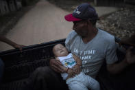 """Guillermo Alonso, 54, cradles his 6-year-old grandson Elvin, in the bed of a pickup truck as they leave the site where his home once stood, in the hillside village of La Reina, Honduras, Thursday, June 24, 2021. His home was obliterated by a mudslide triggered by Hurricanes Eta and Iota. """"We feel sad because we are homeless but the important thing is that the whole family is alive,"""" said Alonso. (AP Photo/Rodrigo Abd)"""
