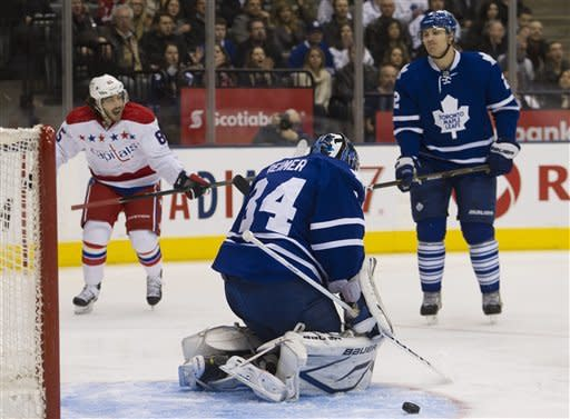 Washington Capitals forward Mattieu Perrealt, left, reacts as Capitals forward Alexander Semin (not shown) scores past Toronto Maple Leafs goalie James Reimer, center, as Maple Leafs defenseman Luke Schenn, right, looks on during first-period NHL hockey game action in Toronto, Saturday, Feb. 25, 2012. (AP Photo/The Canadian Press, Nathan Denette)