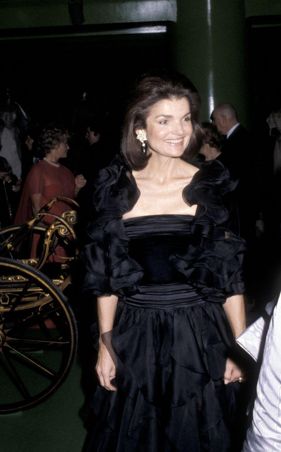 <p>Jackie attends the Costume Institute Gala at the Metropolitan Museum of Art in New York wearing a velvet and chiffon black evening gown with oversize statement earrings. </p>