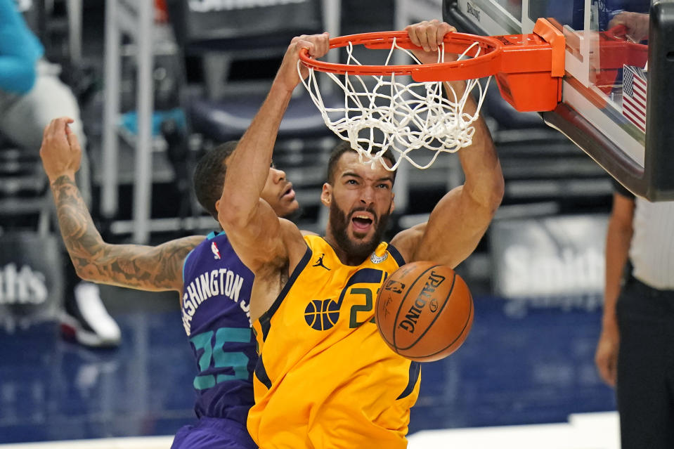 Utah Jazz center Rudy Gobert, right, dunks on Charlotte Hornets forward P.J. Washington (25) in the second half during an NBA basketball game Monday, Feb. 22, 2021, in Salt Lake City. (AP Photo/Rick Bowmer)