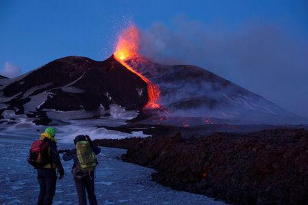 FILE PHOTO: Volcano guides stand in front of Italy's Mount Etna, Europe's tallest and most active volcano, as it spews lava during an eruption on the southern island of Sicily, Italy February 28, 2017. REUTERS/Antonio Parrinello
