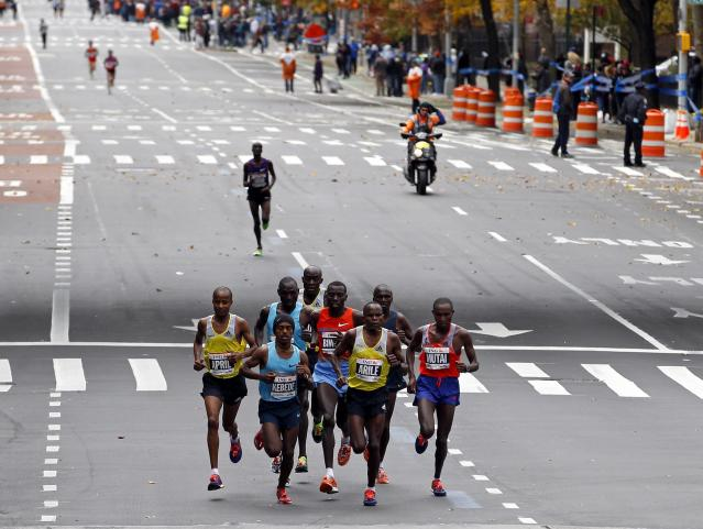 Geoffrey Mutai of Kenya (bottom R) runs with the men's elite pack through the borough of Manhattan during the New York City Marathon in New York, November 3, 2013. Defending champion Mutai and Priscah Jeptoo won the men's and women's races at the New York City Marathon on Sunday for a Kenyan sweep in chilly, windy conditions through the city's five boroughs. REUTERS/Adam Hunger (UNITED STATES - Tags: SPORT ATHLETICS)