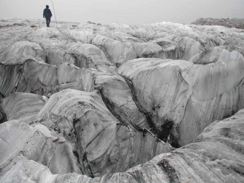 In this Sept. 22, 2018 photo, glaciologist Wang Shijin walks across the Baishui Glacier No.1 on Jade Dragon Snow Mountain in the southern province of Yunnan in China. Scientists say the glacier is one of the fastest melting glaciers in the world due to climate change and its relative proximity to the Equator. It has lost 60 percent of its mass and shrunk 250 meters since 1982. (AP Photo/Sam McNeil)