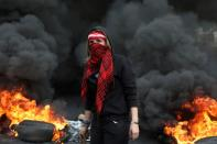 A demonstrator stands near a burning fire during a protest in Zouk