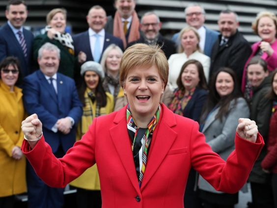Scotland's first minister Nicola Sturgeon celebrates as she joins the SNP's newly elected MPs for a group photo call outside the V&A Museum in Dundee (PA)
