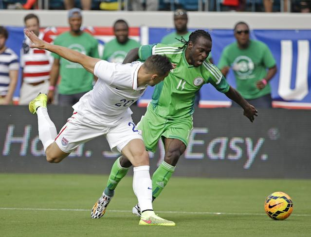 Nigeria's Victor Moses (11) and United States's Geoff Cameron (20) battle for control of the ball during the first half of an international friendly soccer match in Jacksonville, Fla., Saturday, June 7, 2014. (AP Photo/John Raoux)