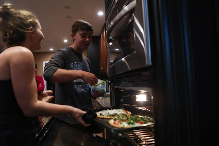 Will Rhodunda checks on the family's pizza dinner with his sister Alexa in their Wilmington, Del., home on June 12.