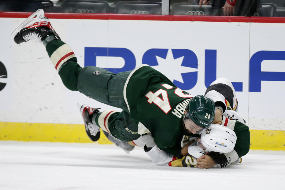 Minnesota Wild defenseman Matt Dumba (24) and Vegas Golden Knights defenseman Alec Martinez (23) fight during the second period in Game 6 of an NHL hockey Stanley Cup first-round playoff series Wednesday, May 26, 2021, in St. Paul, Minn. (AP Photo/Andy Clayton-King)