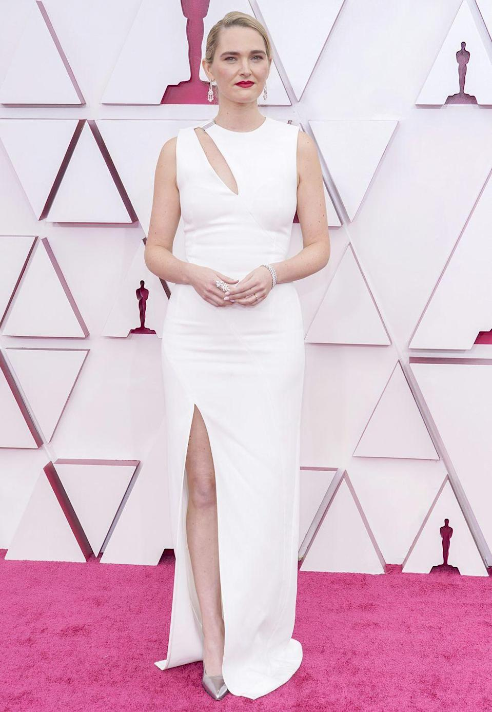 <p>Wearing a white gown with slit details. </p>