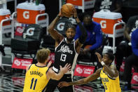 Los Angeles Clippers guard Paul George (13) passes the ball against Indiana Pacers forward Domantas Sabonis (11) and guard Edmond Sumner (5) during the first quarter of an NBA basketball game, Sunday, Jan. 17, 2021, in Los Angeles. (AP Photo/Ashley Landis)