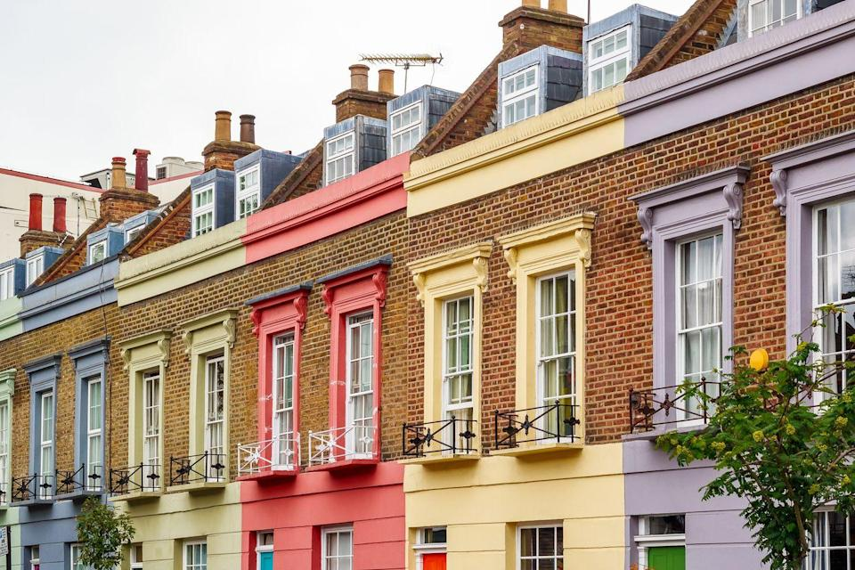 <p>A brick exterior contrasts with pretty pastels on a row of homes in London.</p>