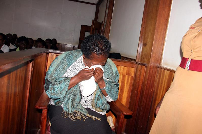 "In this photograph taken on Thursday, March 20, 2014, a Ugandan nurse, Rosemary Namubiru, wipes her eyes in court in the capital Kampala, Uganda. She is accused of injecting a two year old boy Mathew Mushabe with HIV/Aids virus. Goaded by journalists who wanted a clear view of her face, the Ugandan nurse looked dazed and on the verge of tears. The Ugandan press had dubbed her ""the killer nurse"" after the HIV-infected medical worker was accused of deliberately injecting her blood into a two-year-old patient. (AP Photo)"