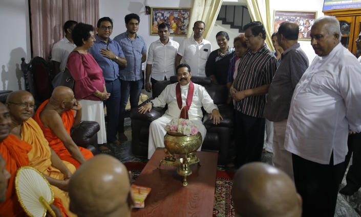 Newly appointed Sri Lankan Prime Minister Mahinda Rajapaksa, center, talks with his supporters at a Buddhist temple in Colombo, Sri Lanka, Friday, Oct. 26, 2018. Sri Lankan President Maithripala Sirisena has sacked the country's prime minister and replaced him with a former strongman, state television said Friday. (AP Photo/Eranga Jayawardena)
