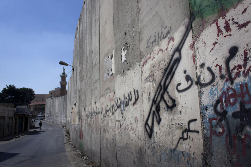 "In this photo taken Monday, Sept. 9, 2013, a Palestinian man walks by a barrier separating the West Bank town of Abu Dis, from east Jerusalem with Arabic graffiti that reads, ""PLO, no for negotiations,"" seen on the side of Abu Dis, West Bank. Twenty years after the two sides signed the Declaration of Principles on the White House lawn, the words that launched Israeli-Palestinian talks on dividing the Holy Land into two states ring hollow to many on both sides. Negotiators said mistakes they made then cause damage to this day. PLO refers to the Palestine Liberation Organization. (AP Photo/Nasser Nasser)"