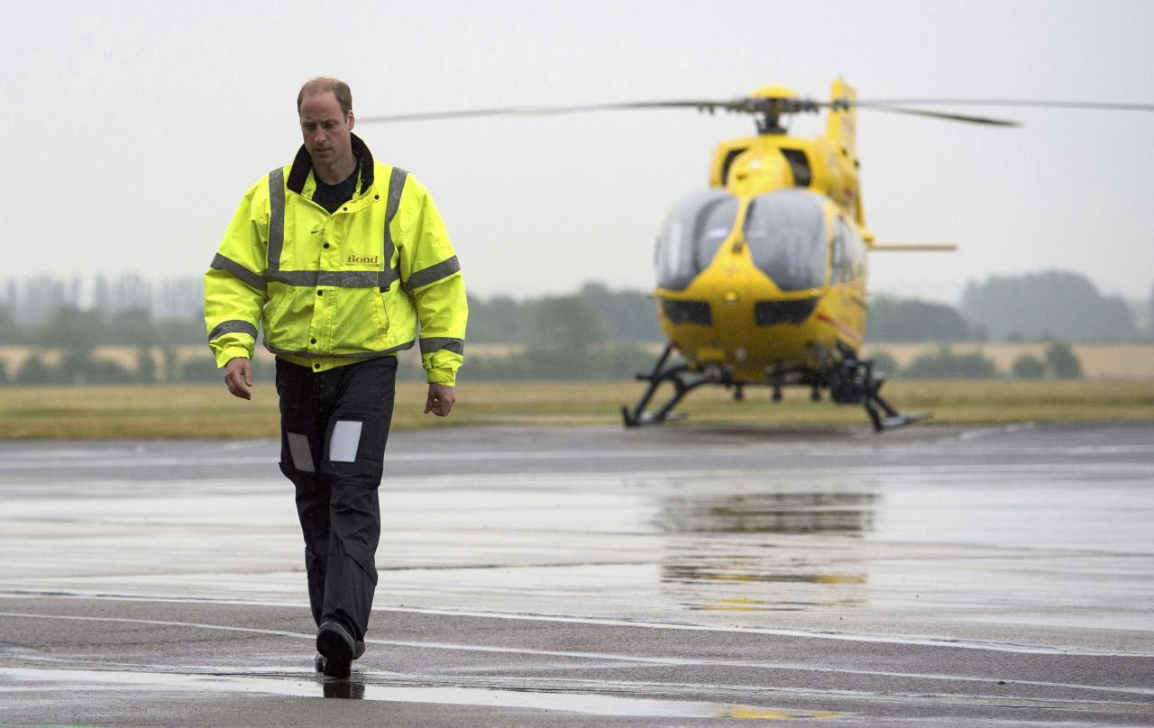 FILE PHOTO: Britain's Prince William walks away from his helicopter as he begins his new job as a co-pilot with the East Anglian Air Ambulance (EAAA) at Cambridge Airport, Britain July 13, 2015.  Stefan Rousseau/pool/File Photo