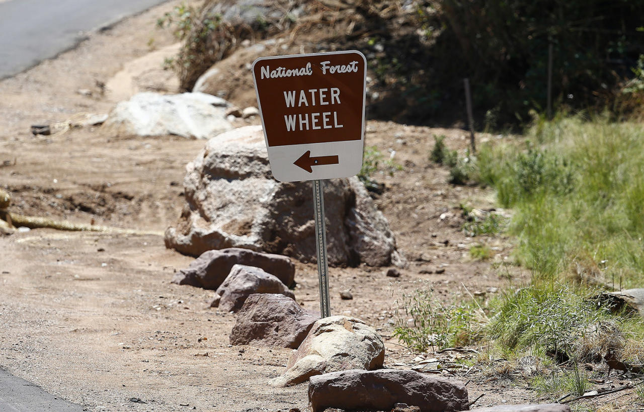 <p>The entrance sign to the Water Wheel recreation area points the the waters where victims were caught in a flash flood along the banks of the East Verde River Monday, July 17, 2017, in Payson, Ariz. The bodies of several children and adults have been found after Saturday's flash flooding poured over a popular swimming area in the Tonto National Forest. (AP Photo/Ross D. Franklin) </p>