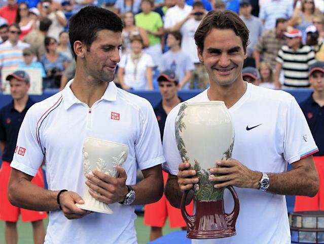 Novak Djokovic, left, from Serbia, and Roger Federer, from Switzerland, pose with their trophies after the men's final at the Western & Southern Open tennis tournament on Sunday, Aug. 19, 2012, in Mason, Ohio. Federer won 6-0, 7-6 (7). (AP Photo/Al Behrman)