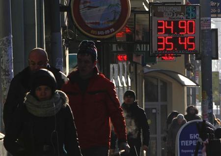 People walk past a currency exchange board showing rouble exchange rates in Moscow