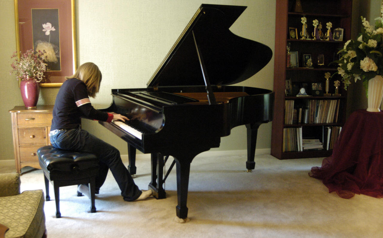"In this March 17, 2005, photo Hillary Adams, the daughter of Aransas County Court-at-Law Judge William Adams, practices the piano at her home in Rockport, Texas. Williams Adams told a Corpus Christi television station the video secretly recorded in 2004 looks ""worse than it is."" The video shows Adams violently whipping his daughter, Hillary, in the legs more than a dozen times, while she screams and refuses to turn over on a bed to be beaten. (AP Photo/The Caller-Times, Rachel Denny Clow)"