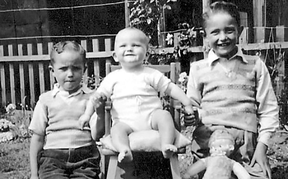 An infant Michael (centre) with his brothers Peter and David
