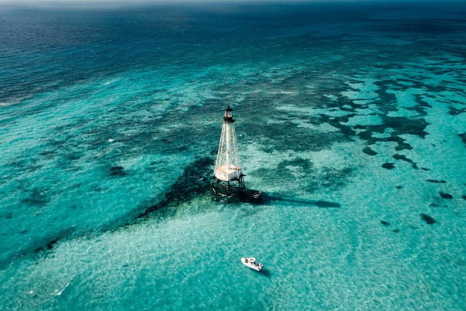 A boat in the clear water near the lighthouse at Alligator Reed, in the Florida Keys