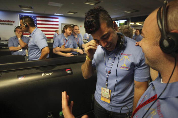 FILE - In this Sunday Aug. 5, 2012 file photo, activity lead Bobak Ferdowsi, center, flight director for the Mars rover Curiosity, in Pasadena, Calif., wipes tears away after the successfull landing of the Curiosity rover on Mars. The Curiosity robot is equipped with a nuclear-powered lab capable of vaporizing rocks and ingesting soil, measuring habitability, and potentially paving the way for human exploration. (AP Photo/Los Angeles Times, Brian van der Brug, File)