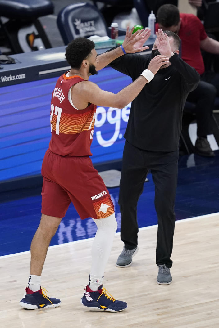 Denver Nuggets coach Michael Malone celebrates with Jamal Murray (27) during the second half of the team's NBA basketball game against the Indiana Pacers, Thursday, March 4, 2021, in Indianapolis. AP Photo/Darron Cummings)