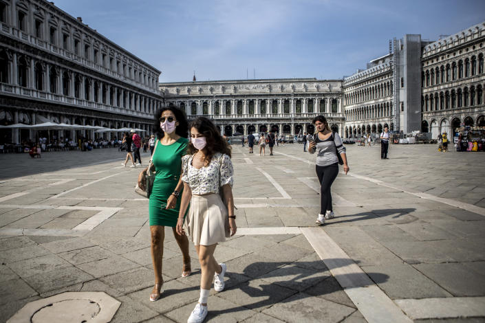 Tourists wearing protective masks walk in San Marco Square in Venice, Italy (Picture: Getty)