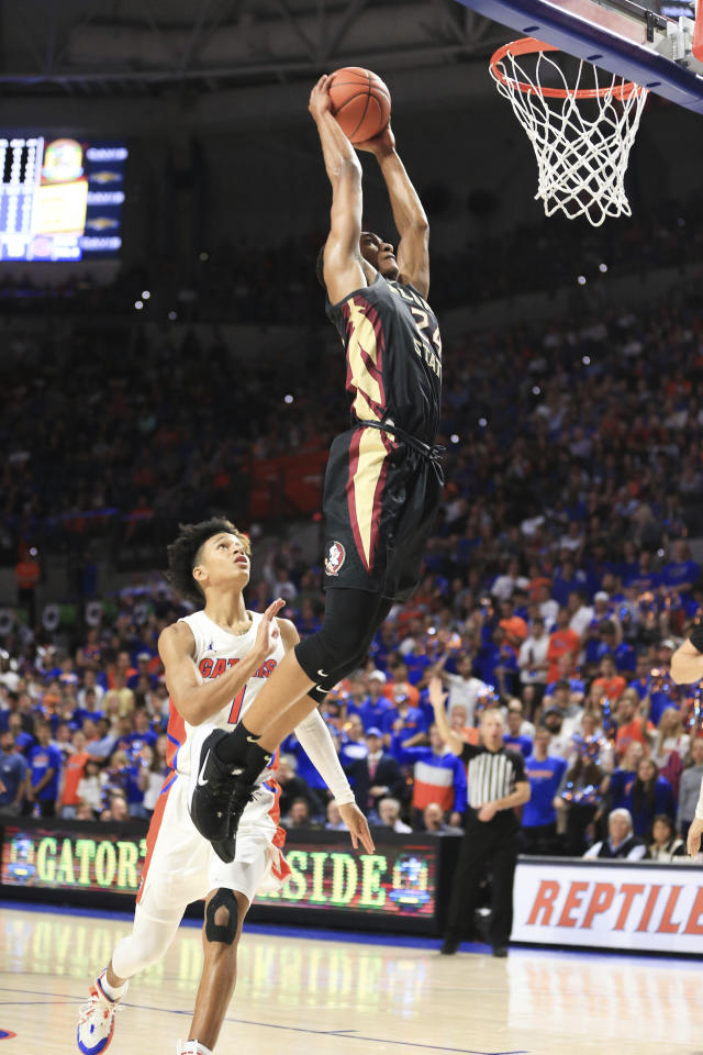 Florida State guard Devin Vassell (24) dunks past Florida guard Tre Mann (1) during the first half of an NCAA college basketball game Sunday, Nov. 10, 2019, in Gainesville, Fla. (AP Photo/Matt Stamey)