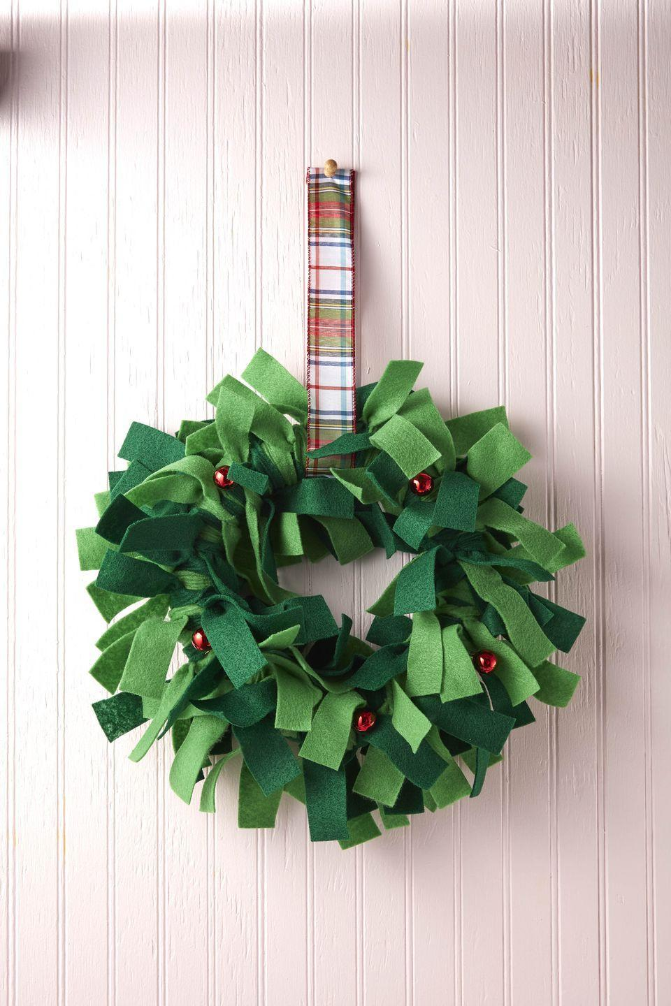 "<p>Simply tie strips of green felt around a wreath form to create this fluffy and fun holiday decor. </p><p><strong>To make:</strong> Cut strips of two different shades of green felt. Tie strips around a wreath form. Attach small red ornaments throughout the wreath with hot glue. Loop a length of wide ribbon around the wreath to hang. </p><p><a class=""link rapid-noclick-resp"" href=""https://www.amazon.com/Greens-Merino-Felt-Sheets-Collection/dp/B01N7X0RIH/ref=sr_1_17?tag=syn-yahoo-20&ascsubtag=%5Bartid%7C10050.g.5030%5Bsrc%7Cyahoo-us"" rel=""nofollow noopener"" target=""_blank"" data-ylk=""slk:SHOP GREEN FELT"">SHOP GREEN FELT</a></p>"