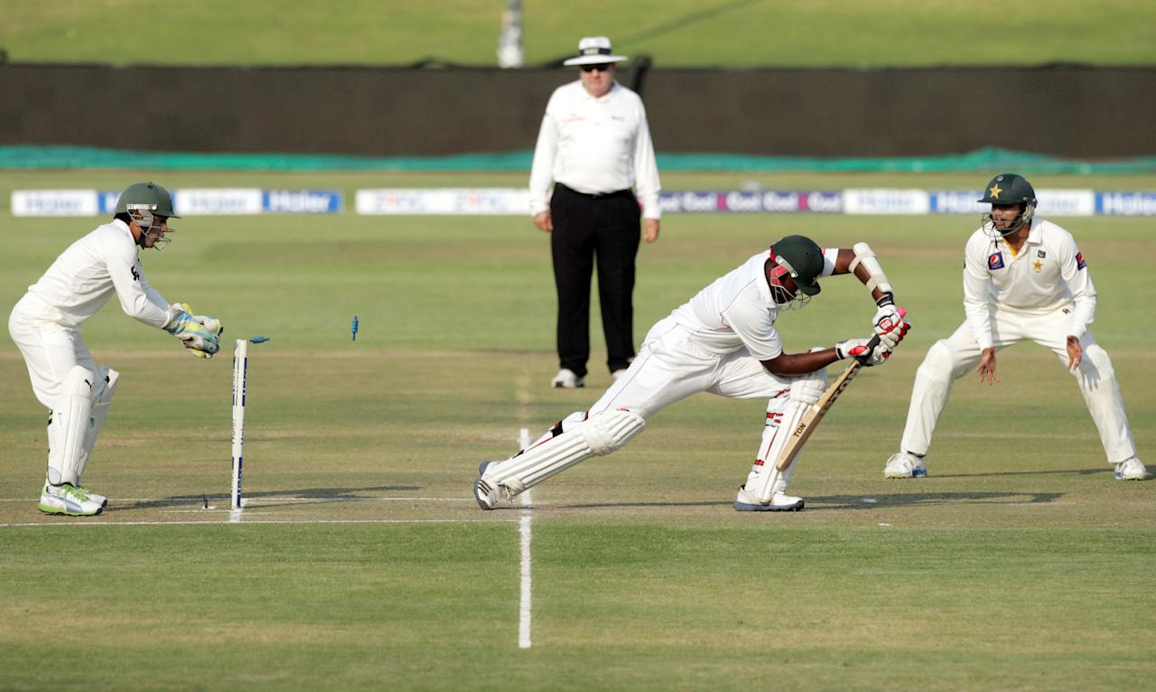 Zimbabwe batsman Hamilton Maskadza (C) survives a stumping attempt by wicket keeper Adnan Akmal (L) during the third day of the second cricket test match between Pakistan and hosts Zimbabwe at the Harare Sports Club September 12, 2013.  AFP PHOTO / JEKESAI NJIKIZANA        (Photo credit should read JEKESAI NJIKIZANA/AFP/Getty Images)