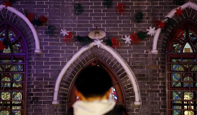 A man stands in front of Christmas decorations at Xishiku cathedral on Christmas Eve in Beijing. Photo: Reuters