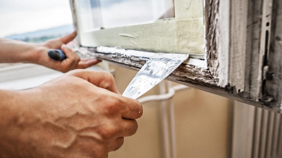 Man using scraper and putty for renovation old windows.