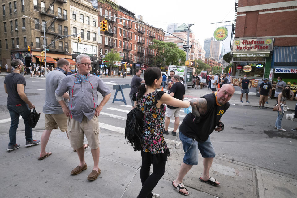 Steve Grillo, right, bumps elbows with a friend in the Hell's Kitchen neighborhood of New York, Friday, May 29, 2020, during the coronavirus pandemic. Grillo lives on the blocked-off street and is a walking advertisement touting his West Side community. (AP Photo/Mark Lennihan)