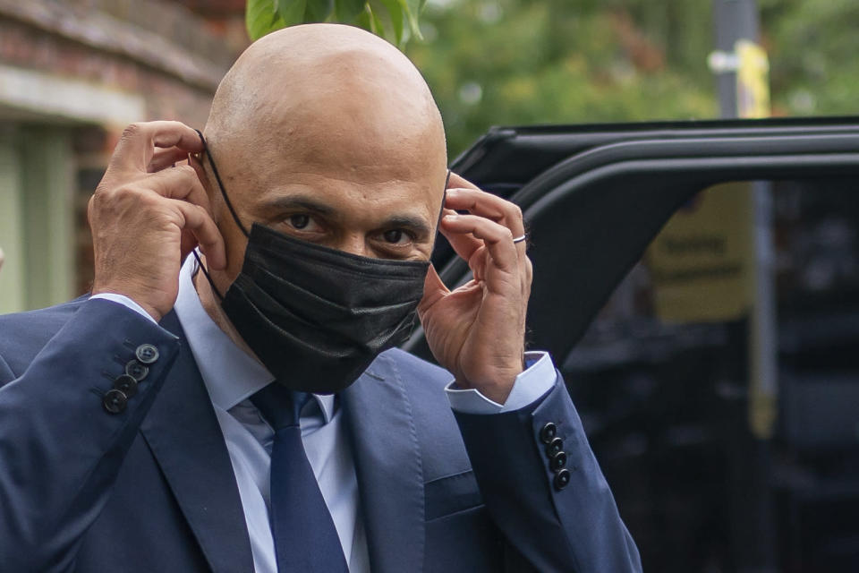Former Chancellor of the Exchequer Sajid Javid puts on a face mask to get into a vehicle, after he was appointed as Secretary of State for Health and Social Care, following the resignation of Matt Hancock, in London, Sunday June 27, 2021. Hancock resigned a day after apologizing for breaching social distancing rules with an aide with whom he was allegedly having an affair. (Aaron Chown/PA via AP)
