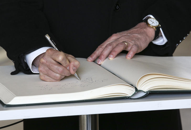 United States Vice President Mike Pence writes in the guest book at the Monument to the Ghetto Heroes after a wreath laying ceremony in Warsaw, Poland, Thursday, Feb. 14, 2019. The Polish capital is host for a two-day international conference on the Middle East, co-organized by Poland and the United States. (AP Photo/Michael Sohn)