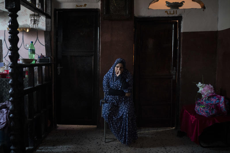 In this Sept. 12, 2018, photo, Amani al-Bilbisi, sits outside her son Mohammed Khader's room as he lays in bed in Gaza City. Mohammed was shot in the leg at one of the demonstrations on Gaza strip's border with Israel. Ever since Hamas launched demonstrations in March against Israel's blockade of Gaza, children have been a constant presence in the crowds. Since then, U.N. figures show that 948 children under 18 have been shot by Israeli forces and 2,295 have been hospitalized, including 17 who have had a limb amputated. (AP Photo/Felipe Dana)