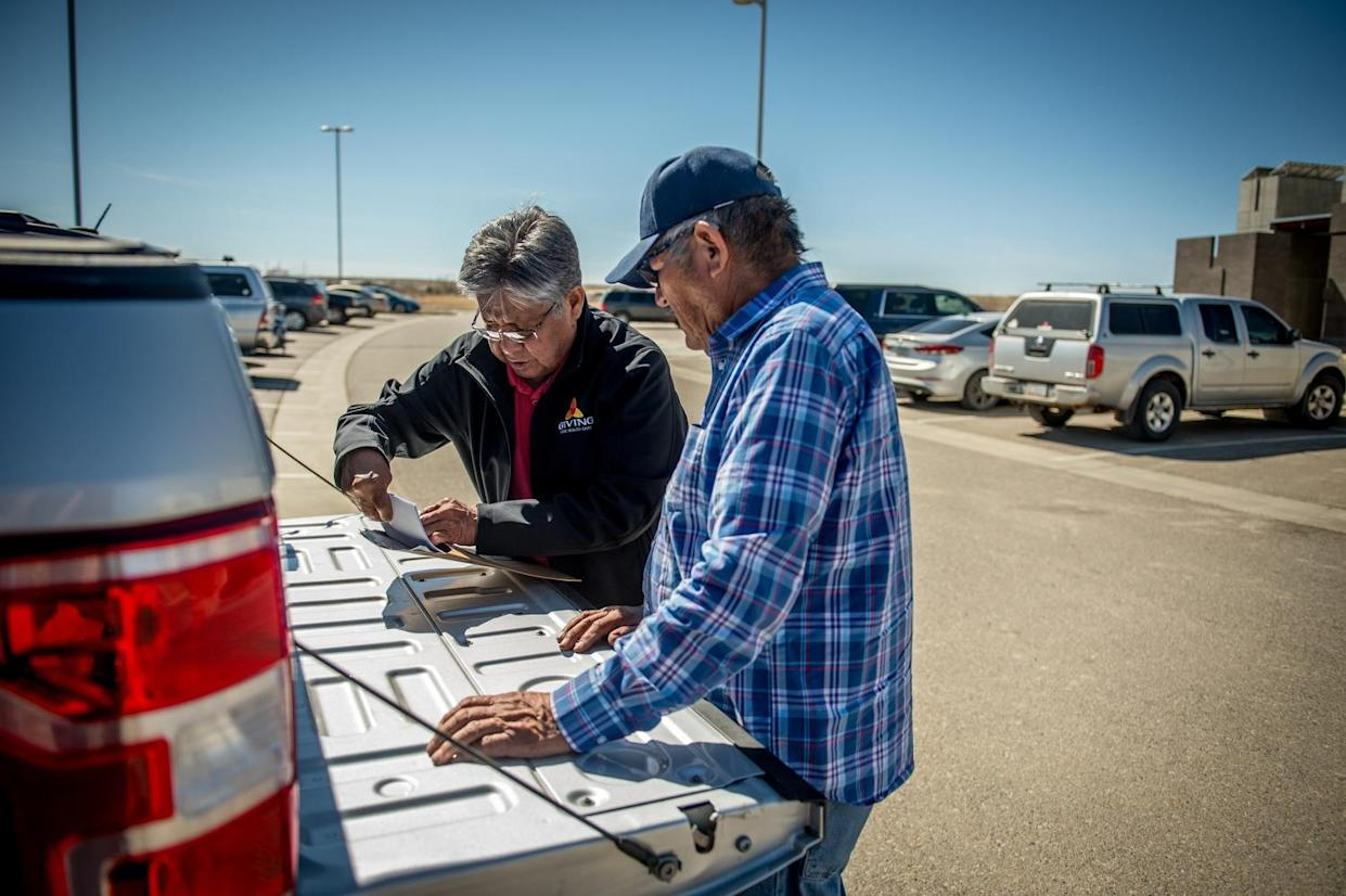 Phil Harrison, left, is pictured assisting a former miner in filing a claim through the Radiation Exposure Compensation Act.(Photograph by Mary F. Calvert)