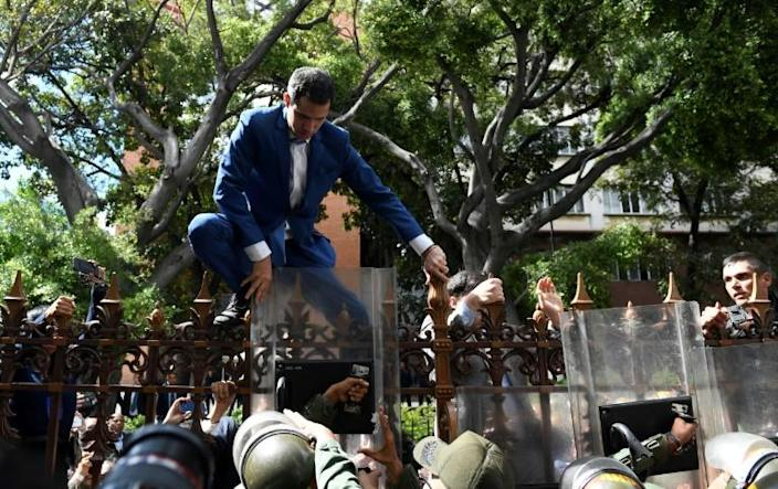 Venezuelan opposition leader and self-proclaimed acting president Juan Guaido is pushed back by police with riot shields as he tries access the National Assembly compound (AFP Photo/Federico Parra)