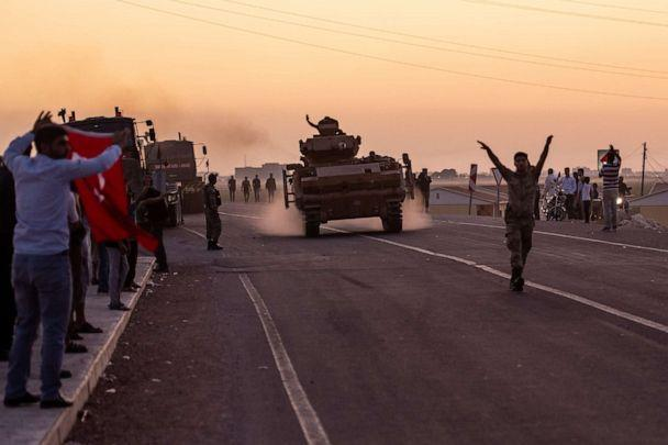 PHOTO: People wave as Turkish soldiers prepare to cross the border into Syria on Oct. 9, 2019, in Akcakale, Turkey. (Burak Kara/Getty Images)
