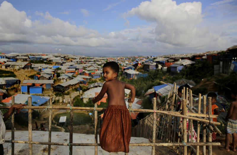 A Rohingya child stands on a bamboo fence overlooking an expanse of makeshift bamboo and tarp shelters at Kutupalong refugee camp, where they have been living amid uncertainty over their future after they fled Myanmar to escape violence a year ago, in Bangladesh, Sunday, Aug. 26, 2018. (AP Photo/Altaf Qadri)