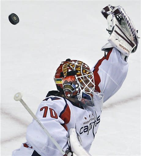 Washington Capitals goalie Braden Holtby (70) reaches up to deflect the puck on a save against the Boston Bruins during the second period of Game 1 of an NHL hockey Stanley Cup first-round playoff series in Boston, Thursday, April 12, 2012. (AP Photo/Charles Krupa)