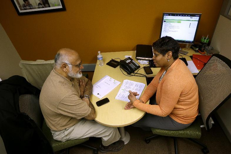 This photo taken Jan. 9, 2013 shows H&R Block Tax preparer Tracey Wales, right, working with customer Muneer Sheikh, on preparing his taxes, at H&R Block office downtown in Washington. Taxpayers preparing to file their 2012 returns can breathe a collective sigh of relief. The alternative minimum tax or AMT has been patched, permanently, and several tax credits and deductions that technically expired at the end of 2011 were extended as part of the fiscal cliff legislation that Congress passed and President Barack Obama signed into law in January 2013. (AP Photo/Pablo Martinez Monsivais)