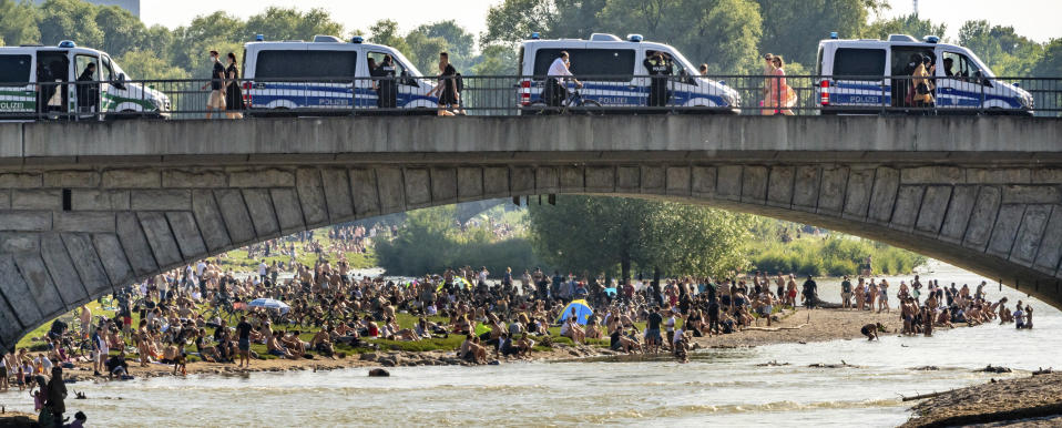 Police cars stand on a bridge next to hundreds of people staying at the banks of the river Isar after ongoing relaxing of measures against the coronavirus outbreak in Munich, Germany, Saturday, June 13, 2020. (Peter Kneffel/dpa via AP)