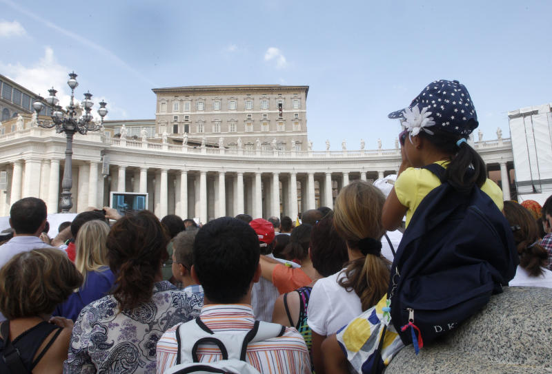 """A crowd listens to Pope Francis, small figure seen at the second from right window, reciting the Angelus prayer from his studio window overlooking St.Peter's Square at the Vatican, Sunday, Sept. 1, 2013. Francis is asking people to join him next weekend in a day of fasting for peace in Syria. The pontiff invited people of all faiths to join him Saturday evening in St. Peter's Square to invoke the """"gift"""" of peace for Syria, the rest of the Middle East and worldwide where there is conflict. (AP Photo/Riccardo De Luca)"""