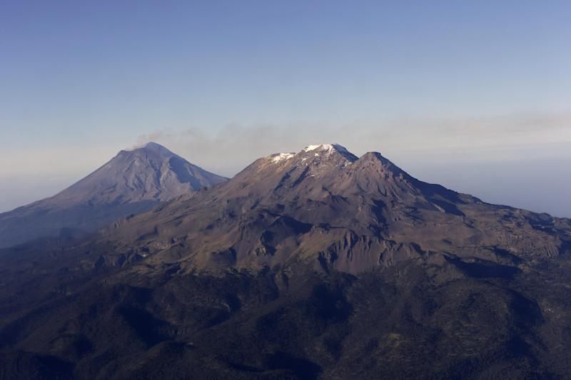 "FILE - In this July 23, 2013 file photo, smoke rising from the crater of the Popocatepetl volcano is carried away by wind, next to dormant Iztaccihuatl volcano, front right, seen from a Mexican Navy aircraft on a volcano monitoring mission in Mexico. According to Mexican legend, Popocatepetl was a warrior who sought the hand of Iztaccihuatl, a fair maiden whose reluctant father told her that her suitor had died in battle. The ""Romeo and Juliet""-style tale ends with the lovers turning into twin mountains east of Mexico City. (AP Photo/Dario Lopez-Mills, File)"