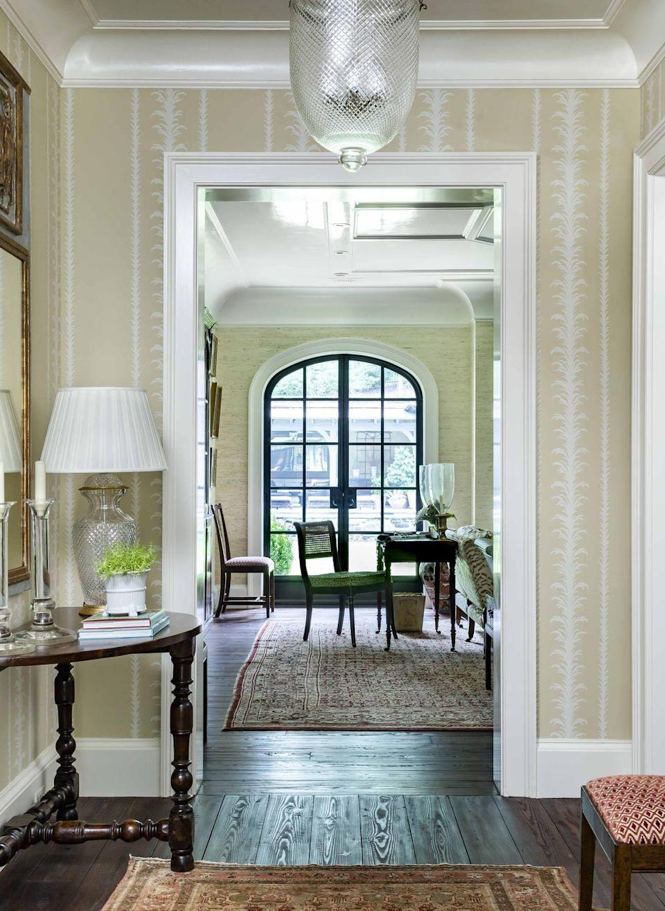 <p>Patterns and architecture go hand in hand. Here, an enfilade space is accented with a columnar wallpaper (George Spencer Designs) that has a ground color that's repeated in the arrowroot wallcovering seen in the room beyond. </p><p>Taking tones and hues in the same family from room to room carries the eye's gaze, as does an architectural enfilade. Trim painted in a satin finish adds a luster to the millwork.</p>
