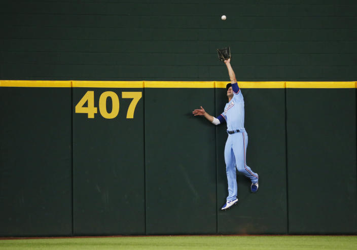 Texas Rangers centerfielder Eli White attempts to catch a home run by Oakland Athletics' Jed Lowrie during the second inning of a baseball game in Arlington, Texas, Sunday, July 11, 2021. (AP Photo/Ray Carlin)